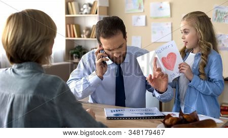 Father Ignoring Daughter With Greeting Card, Talking On Phone, Indifference
