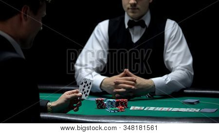 Overconfident Businessman Having Bad Hand Combination But Making Bet At Poker