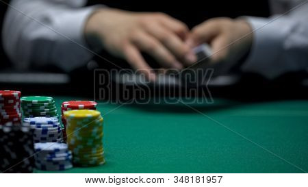 Professional Casino Croupier Shuffling Cards Before Poker Game, Background