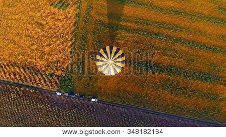 Envelope Of Hot Air Balloon Landed Floating In Air, Casting Shadow Over Field