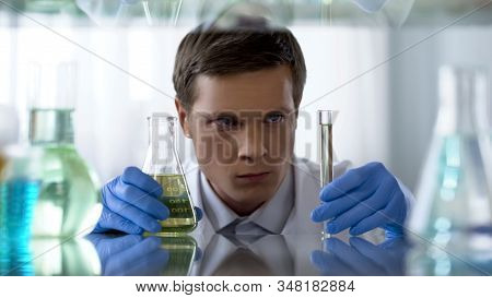 Unsure Scientist Looking At Chemical Substance In Test Tube Waiting For Reaction