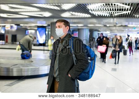 Young European Man In Gray Coat, Protective Disposable Medical Mask In Airport. Afraid Of Dangerous