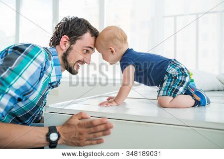 Positive Young Dad Sits With His Little Son And Plays While Lying On The Living Room Floor. The Conc