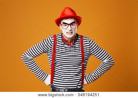 Young mime in white gloves and red hat on orange background