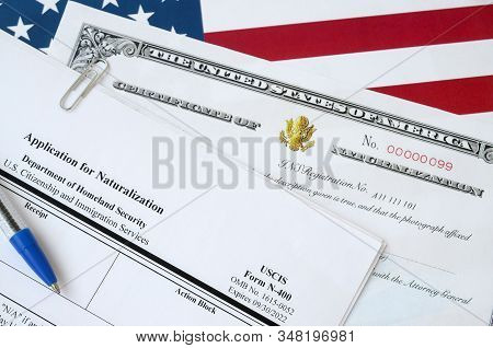 N-400 Application For Naturalization And Certificate Of Naturalization Lies On United States Flag Wi