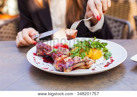 Woman Eat Healthy Lunch In Restaurant. Grilled Meat Steak With Cranberry Sauce, Glazed Peaches And A