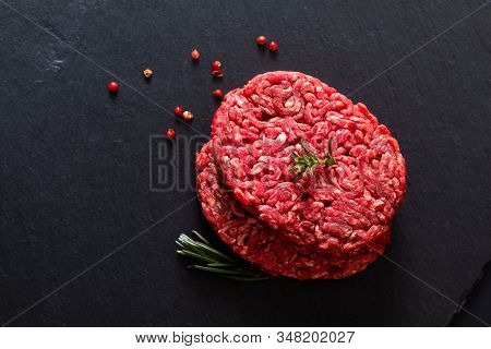 Food Concept Organic Raw Minced Or Ground Beef Grass Feed Burger On Black Slate Stone With Copy Spac