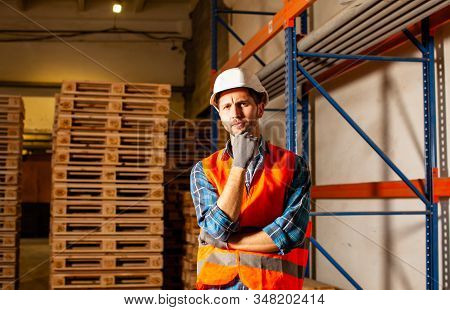 Thoughtful Worker In Protective Uniform In The Warehouse