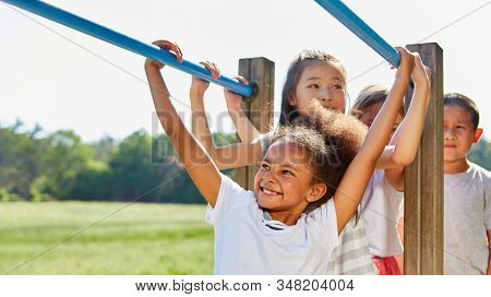 Group of children turns on climbing frame in summer camp or summer camp