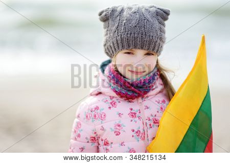 Cute Little Girl Celebrating Lithuanian Independence Day Holding Tricolor Lithuanian Flag On The Sho