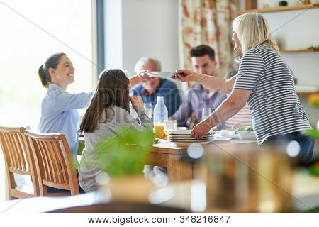 Happy extended family at the dining table having lunch or dinner