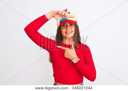Young beautiful girl wearing fanny cap with propeller standing over isolated white background smiling making frame with hands and fingers with happy face. Creativity and photography concept.