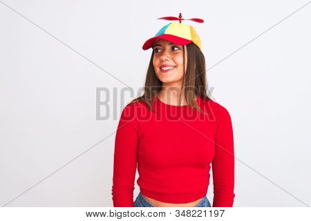 Young beautiful girl wearing fanny cap with propeller standing over isolated white background looking away to side with smile on face, natural expression. Laughing confident.