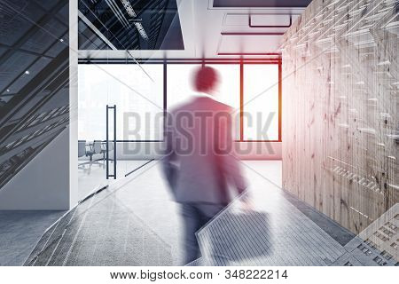 Blurry Young Businessman Walking In Modern Office Hall With White And Wooden Walls, Panoramic Window
