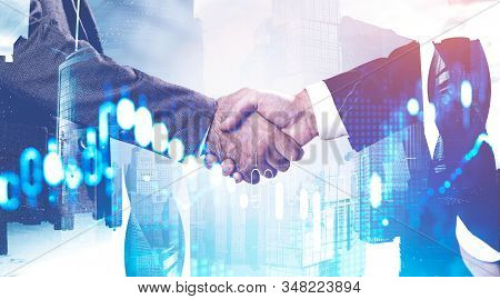 Close Up Of Two Businessmen Shaking Hands In Moscow City With Double Exposure Of Blurry Digital Char