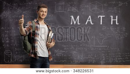 Male student showing thumbs up in front of a blackboard written with math formulas and equations and text math