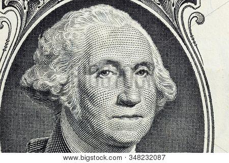 Macro close up photograph of George Washington on the US one dollar bill.
