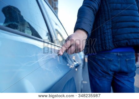 Bad Guy Scratching The Car Door With A Screwdriver In The Parking Lot On The Street. Damage Of Prope