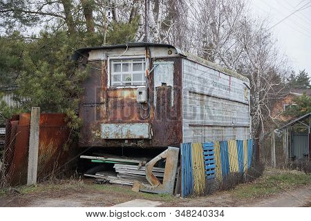 One Old Rusty Metal Trailer With A Window On The Street Near A Fence In The Grass