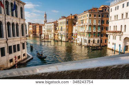 Gondolas And Boats Float On Grand Canal In Venice, Italy. View Through Rialto Bridge Railing