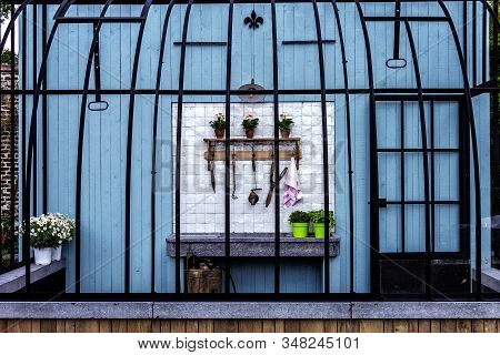 A Portrait Of An Open Outdoor Gardening Shed. The Shed Is Made Of A Wooden Wall And Bars Like A Bird