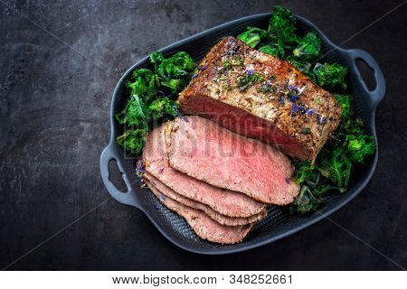 Traditional Commonwealth Sunday roast with sliced cold cuts roast beef with kalette and herbs as top view on a modern design pan with copy space left