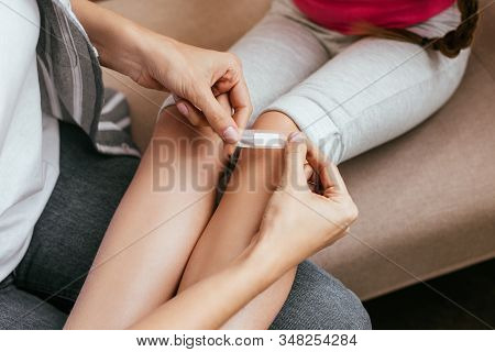 Cropped View Of Mother Applying Adhesive Bandage On Knee Of Daughter