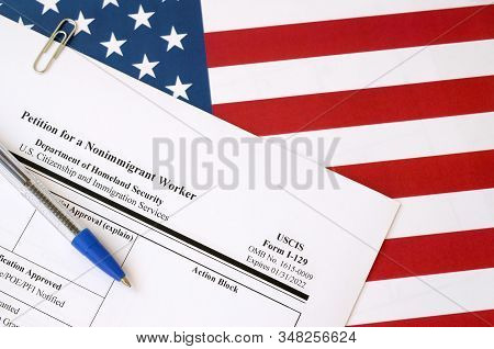 I-129 Petition For A Nonimmigrant Worker Blank Form Lies On United States Flag With Blue Pen From De