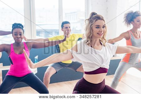 Selective Focus Of Multiethnic Dancers Smiling While Practicing Zumba In Dance Studio