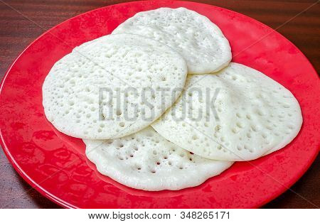 Kerala Special Appams In A Red Plate On A Wooden Table Ready To Be Eaten.