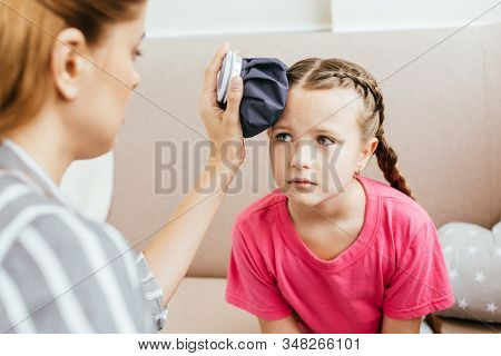 Mom Holding Ice Bag Compress On Head Of Sad Daughter With Headache