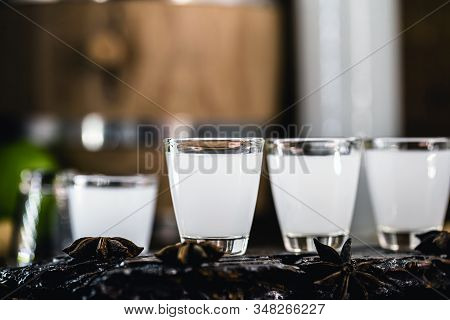 Traditional Greek Vodka, Known As Uzo Or Ouzo In Shot Glasses On A Rustic Wooden Background. Space F