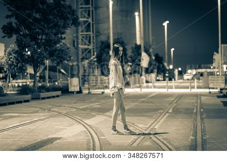 Gritty Monochrome Image Of Trendy Teenager Walking Across Area With Old Railway Tracks With Industri