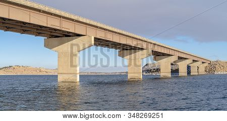 Stringer Bridge Spanning Over A Lake With View Of Snowy Terrain And Cloudy Sky