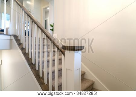 Indoor Staircase Of A Home With White Balusters Brown Handrail And Newel