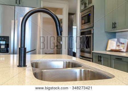 Kitchen Island Sink With Double Bowl And Black Faucet Against Kitchen Appliances
