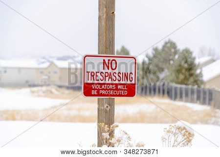 No Trespassing Sign On Wooden Post Against Blurry Snowy Property In Winter