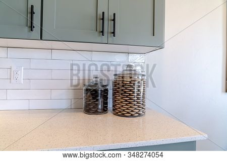 Jars Of Cookies On Kitchen Counter Top Against Tile Backsplash And White Wall