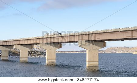 Panorama Stringer Bridge Supported By Abutments Ovelooking Lake Land And Cloudy Sky