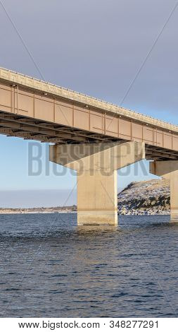 Vertical Frame Stringer Bridge Spanning Over A Lake With View Of Snowy Terrain And Cloudy Sky