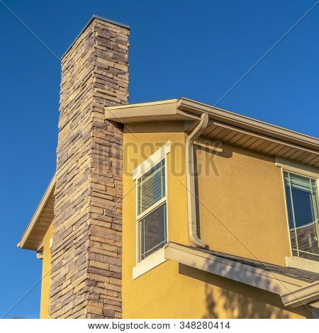 Square Frame Home Exterior With Stone Brick Chimney Against Gable Roof And Yellow Wall