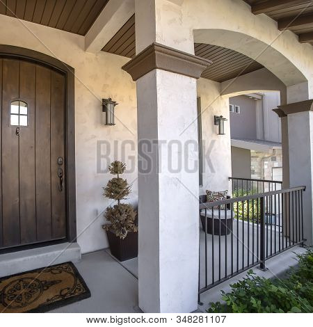 Square Frame Brown Wood Arched Front Door With Glass Panes At The Facade Of Home With Porch