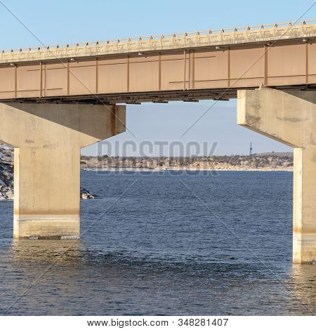 Square Focus On A Beam Bridge Supported By Abutments Over Blue Lake Against Cloudy Sky