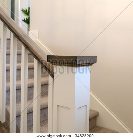 Square Indoor Staircase Of A Home With White Balusters Brown Handrail And Newel