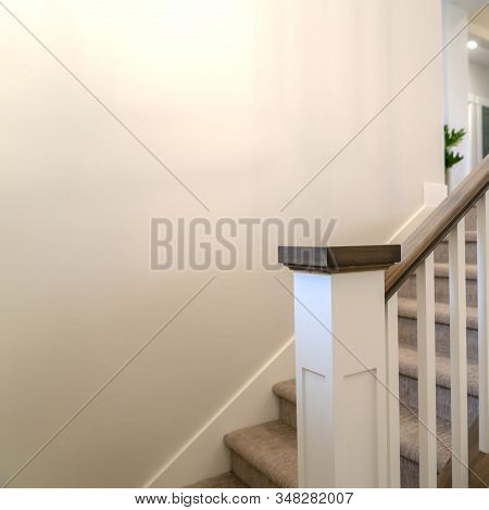 Square Frame Indoor Staircase Of A Home With White Balusters Brown Handrail And Newel