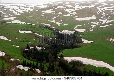 Panorama Of Green Tableland With Rest Of Snow During Spring In Mountains