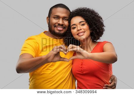 love, valentines day and people concept - happy african american couple making hand heart gesture over grey background