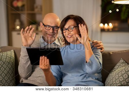 technology, old age and people concept - happy smiling senior couple with tablet pc computer having video call at home in evening