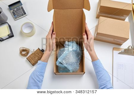 delivery, mail service, people and shipment concept - female hands packing mug into parcel box with protective bubble wrap at post office