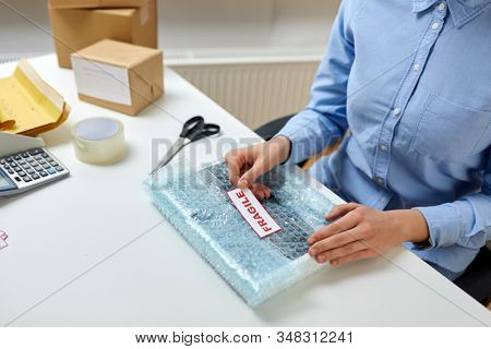 delivery, mail service, and shipment concept - close up of woman sticking fragile mark to parcel in protective bubble wrap at post office